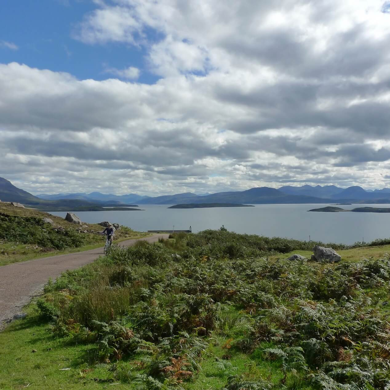 Folding bike cyclist ascends a single track road with the Summer Isles and Torridon in the background
