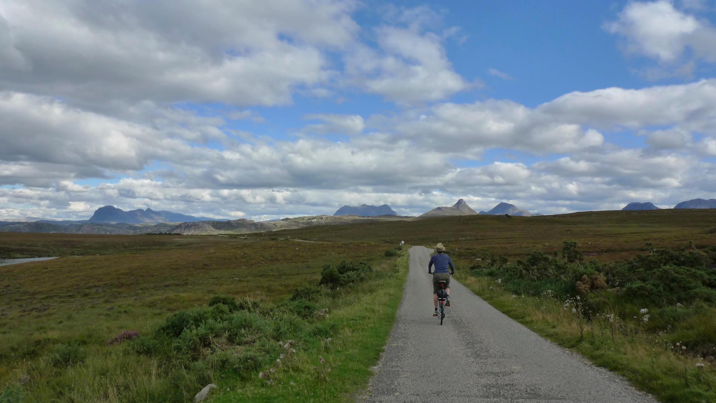 Folding bike on a single track road with mountains of Assynt in the background