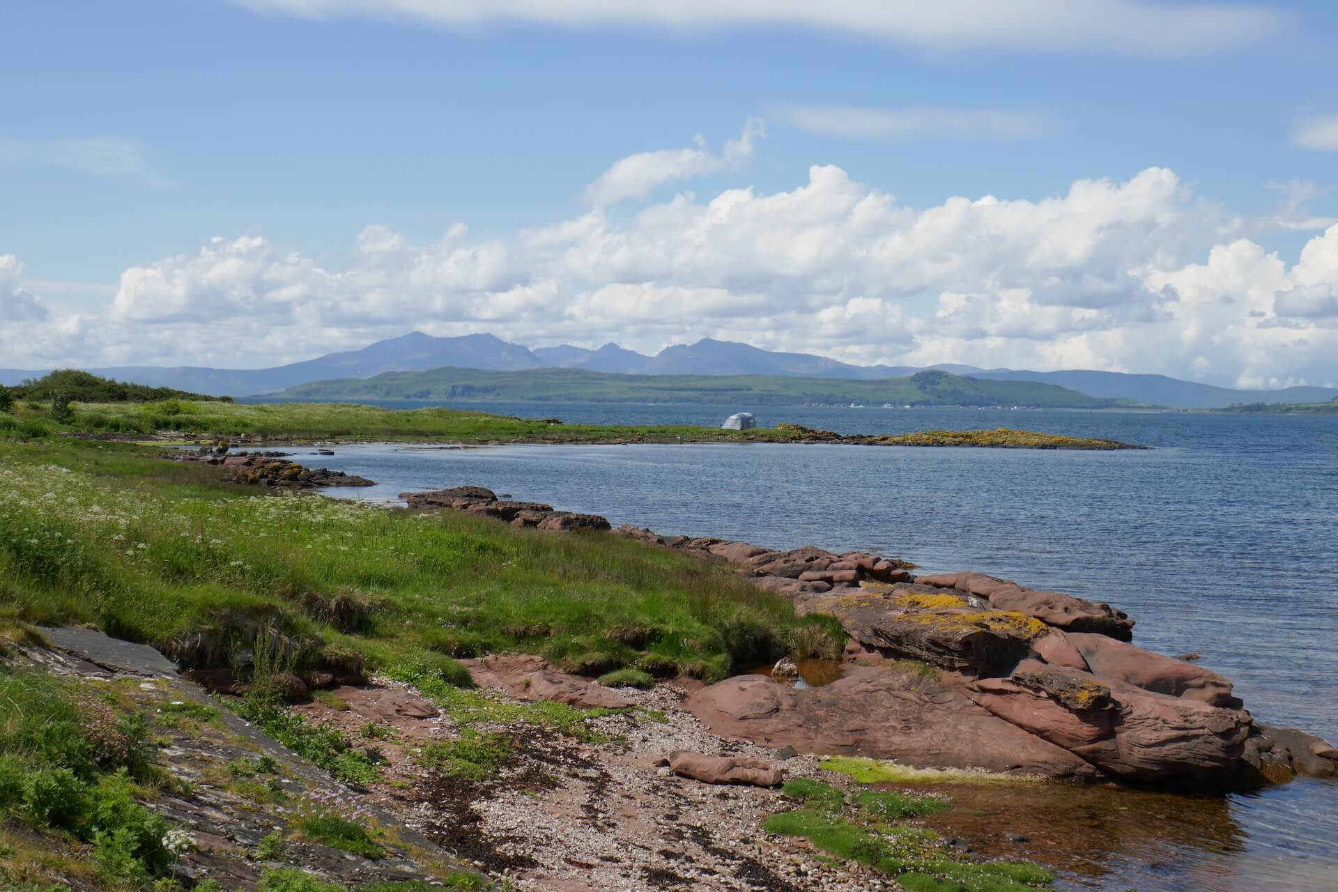 Sandstone coast of Isle of Cumbrae with Isle of Arran in the distance
