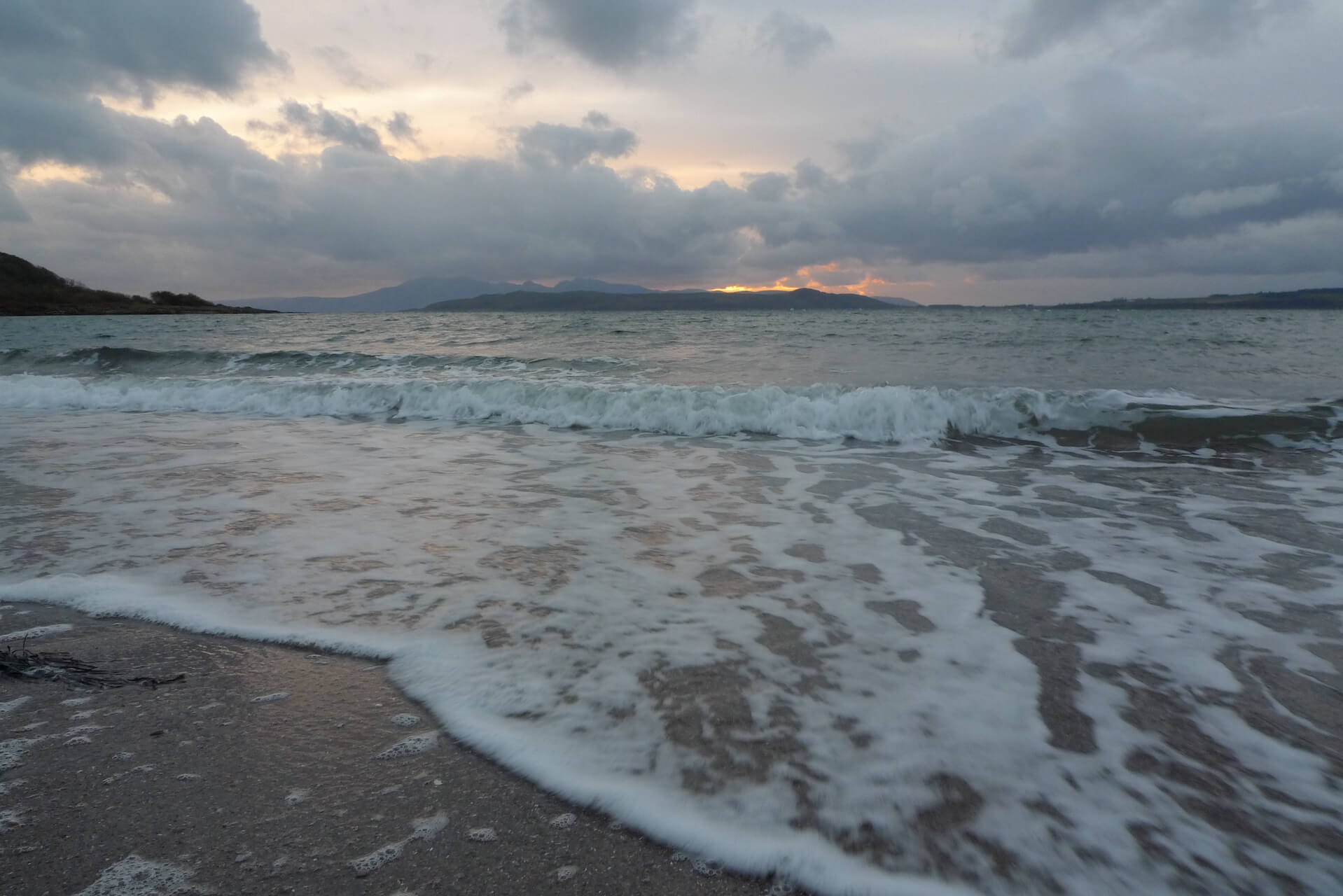 Stormy sunset sky as seen from a frothy beach on Isle of Cumbrae